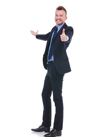 full length picture of a young business man presenting something in the back while showing the thumb up gesture to the camera along with a smile. on white background photo