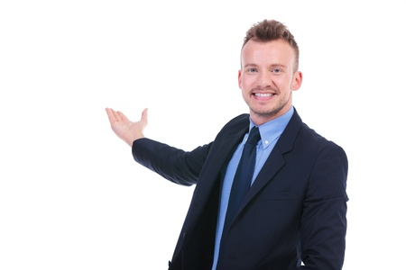 executive: young business man presenting something in the back while smiling for the camera. on white background