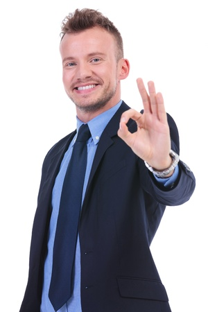 young business man showing the ok gesture with a smile on his face. on white background photo