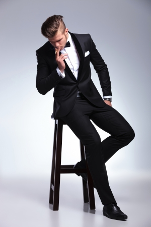 the stool: elegant young fashion man in tuxedo sitting on stool and smoking a cigar while looking down, away from the camera. on gray background