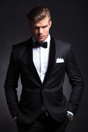 elegant young fashion man in tuxedo is holding both hands in his his pockets and looking at the camera.on black background photo