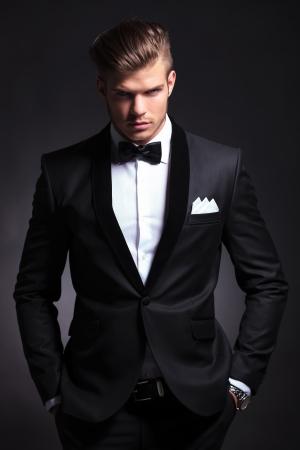 elegante moda giovane uomo in smoking è in possesso di entrambe le mani in tasca e guardando lo sfondo camera.On nero