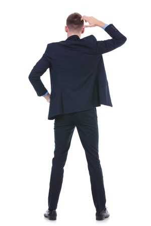 questioning: back view full length picture of a young business man standing with a hand on his hip and scratching his head with the other. on white background Stock Photo