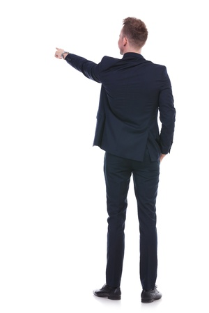 indicating: back view full length picture of a young business man pointing forward while holding a hand in his pocket. on white background