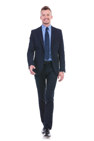 full length picture of a young business man walking towards the camera with a smile on his face. on white background
