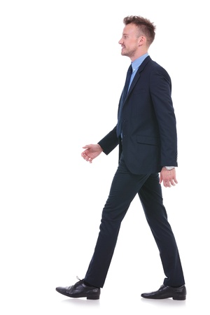 side view full length picture of a young business man walking and looking forward . on white background
