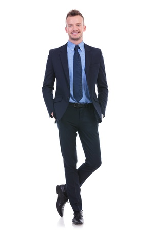 full length picture of a young business man standing with legs crossed and both hands in his pockets while smiling at the camera. on white background photo