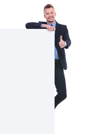 full length picture of a young business man holding a big empty pannel and the thumb up gesture while smiling at the camera. on white background photo