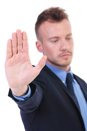 no pase: Hombre de negocios joven que muestra su mano mientras mira a la cámara. en el fondo blanco Foto de archivo
