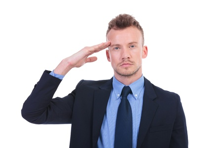 Salute: young business man saluting with hand at eyebrow. on white background