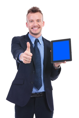 young business man showing a tablet and the thumb up gesture while smiling at the camera. on white background photo