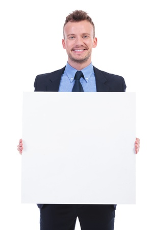pannel: young business man holding a blank pannel with both hands and smiling at the camera. on white background