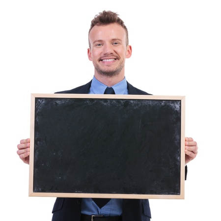 young business man holding a blackboard in his hands and smiling to the camera. on white background photo