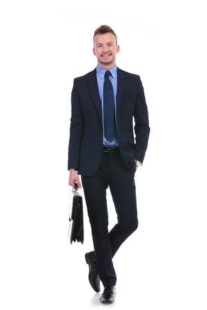 full length picture of a young business man smiling for the camera with a suitcase in his hand and a hand in his pocket. on white background photo
