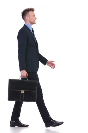 full length side view picture of a young business man walking with a suitcase in his hand and a smile on his face. on white background