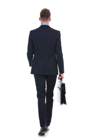 full length rear view picture of a young business man walking away from the camera with a suitcase in his hand. on white background