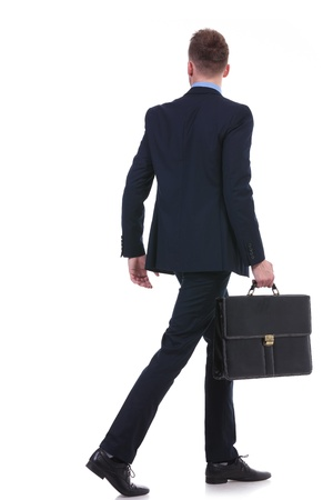 full length back view picture of a young business man with a suitcase in his hand walking away. on white background photo