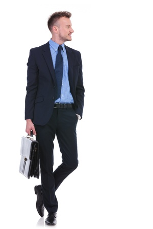 brief case: full length picture of a young business man holding a briefcase in a hand and the other in his pocket while looking to his side, away from the camera. on white background Stock Photo