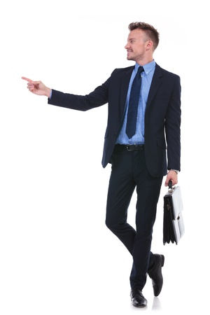 full length picture of a young business man holding a suitcase and pointing and looking to his side. on white background photo