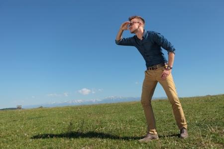 lejos: hombre joven ocasional al aire libre mirando a lo lejos con la mano sobre los ojos Foto de archivo