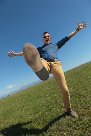 goofing: casual young man standing in a leg outdoor in the grass while holding his arms opened and screaming Stock Photo