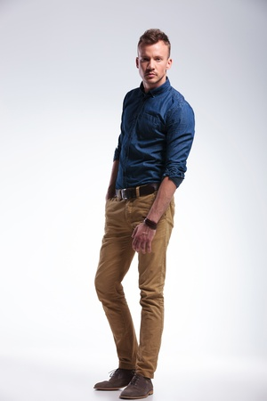 standing man: full length photo of a casual young man standing in the studio with a hand in his pocket and looking at the camera. on gray background Stock Photo