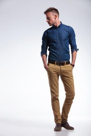 modellini: ritratto a figura intera di un giovane uomo casual in piedi con entrambe le mani in tasca guardando al suo fianco, di distanza dalla fotocamera. su sfondo grigio
