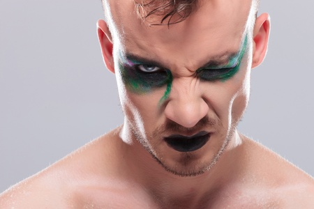 twitch: closeup of a casual young man with dramatic makeup looking at the camera with one eye. on gray background Stock Photo