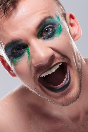 odd: closeup of a casual young man with dramatic makeup laughing out loud with mouth opened. on gray background Stock Photo