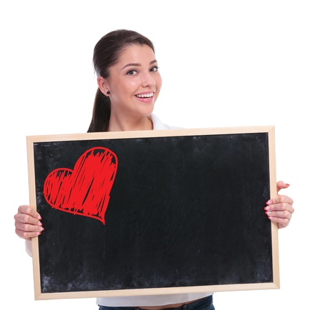 both: casual young woman holding a small blackboard with a red heart drawn on it while smiling to the camera. isolated on white background