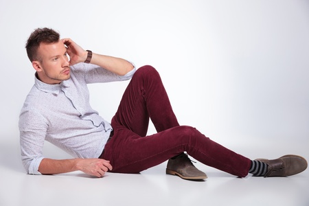 sitting on the ground: casual young man laying on the floor and looking away from the camera. on gray background