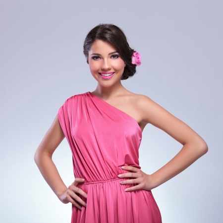 young beauty woman wearing a cute pink dress and a rose in her hair smiles for the camera with her hands on her hips. on a light gray background photo