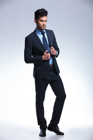 lapels: full length picture of a young business man holding his hands on the lapels of his jacket while looking at the camera. on a gray background