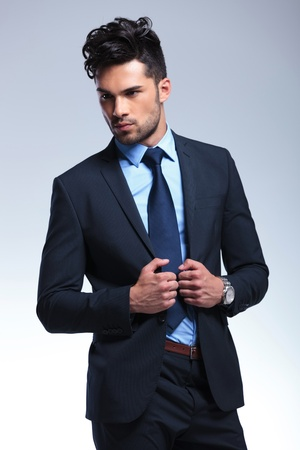 lapels: young business man looking away while holding his hands on his lapels. on a gray background