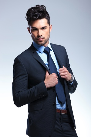 lapels: young business man holding his jacket by its lapels and looking at the camera. on a gray background