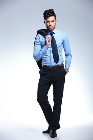 traje: foto de cuerpo entero de un joven hombre de negocios la celebraci�n de su chaqueta sobre el hombro y la mano en el bolsillo mientras mira a la c�mara. sobre un fondo gris