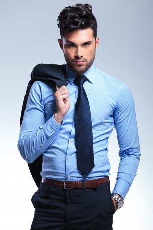 formal: young business man hanging his jacket on his shoulder and holding a hand in his pocket while looking at the camera. on a gray background Stock Photo