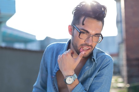 unbuttoned: casual young man posing outdoor with a hand on his lower lip while looking at the camera