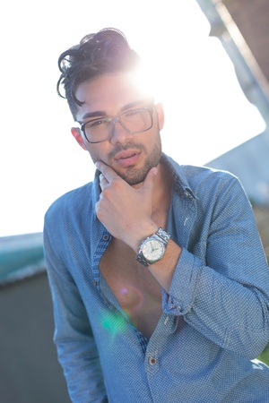unbuttoned: casual young man posing outdoor with his hand on his unshaven face while looking at the camera