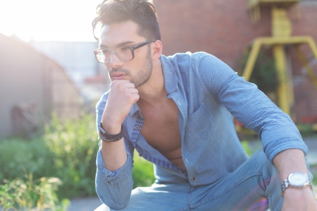 unbuttoned: casual young man outdoor standing with his hand on his chin and pensively looking away from the camera
