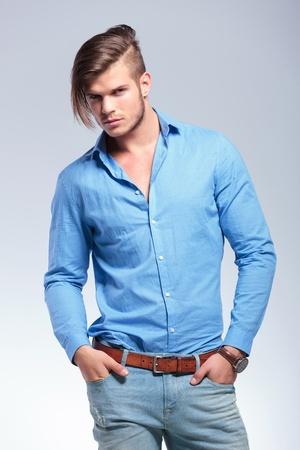 hezk�: mladý muž, příležitostná při pohledu na fotoaparát s oběma rukama v předních kapes. na šedém pozadí studio