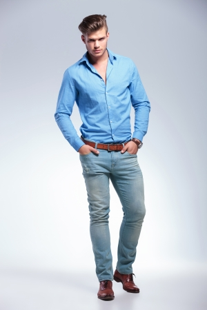 both: full length photo of young casual  man with both hands in his pockets looking at the camera. on gray studio background Stock Photo