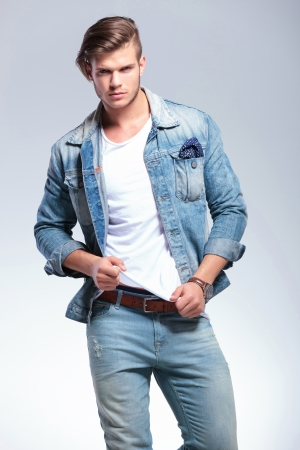 attractive casual young man pulling on his shirt while looking at the camera. on gray background photo