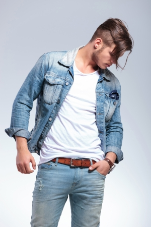 side pose: attractive casual young man with a hand in his pocket looking down, away from the camera. on gray background