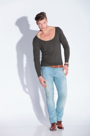 full body picture of a casual young man on gray studio background with shadow photo