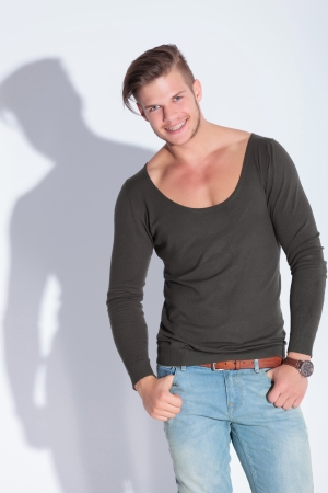 casual young man with thumbs in pockets shows the camera a toothy smile. on gray studio background with shadow