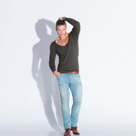 full body picture of a casual young man holding his hair while looking at the camera with a hand in his pocket. on gray studio background with shadow photo