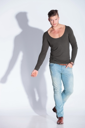 full body picture of a casual young man holding one hand in his pocket while looking at the camera. on gray studio background with shadow photo