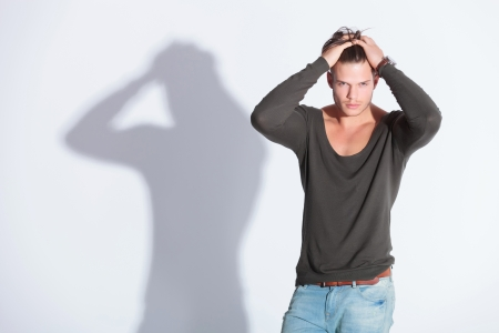 casual young man with his hands in his hair looking at the camera. on gray studio background with shadow