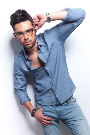adjusting: casual young man posing with a thumb in his pocket and a hand on his eyeglasses while looking at the camera. on gray background
